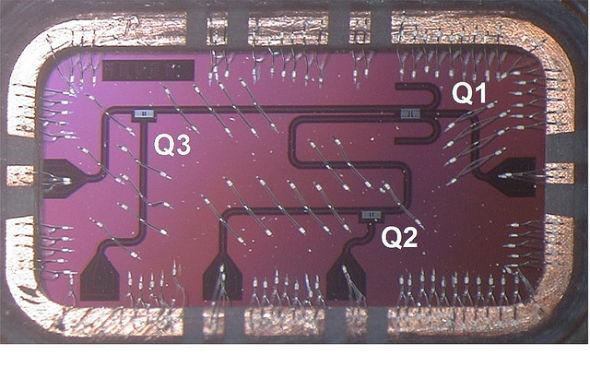 一个硅芯片,容纳3个量子比特。这个芯片倒装在印刷线路板上,通过丝焊(8×4毫米)连接I/O同轴电缆。更大规模的量子比特和振荡电路集成可用于打造具有可升级性的系统